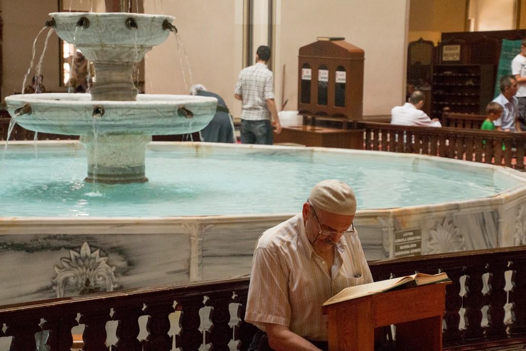 Een oude man leest de koran in een moskee in Bursa