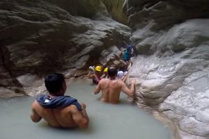 Klimmen en glijden door het water en de smalle openingen