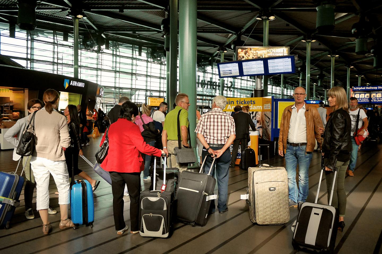 Reizigers wachten op Schiphol