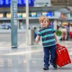 Kind op vliegveld met een koffer