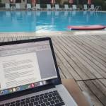 Met de laptop aan het zwembad