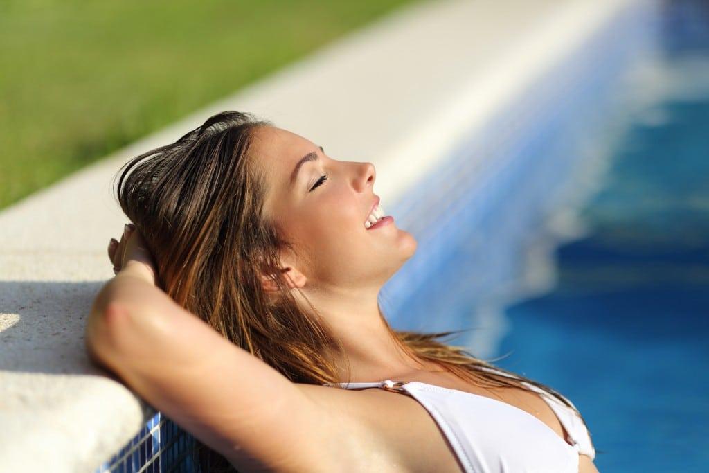 Vrouw geniet in zwembad van de zon