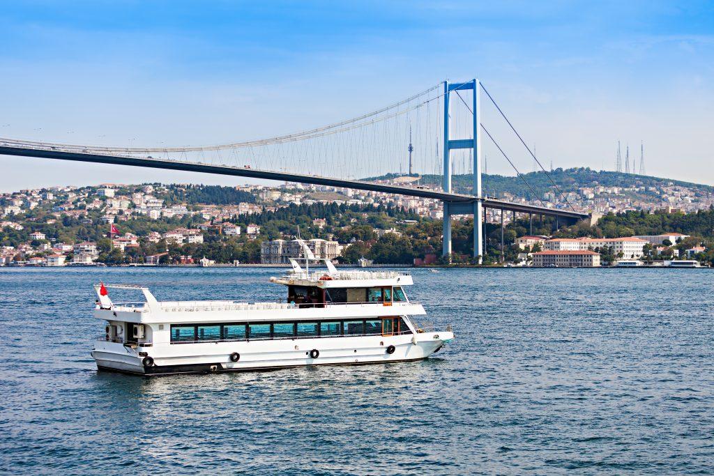 Rondvaartboot bij de Bosporus brug in Istanbul, Turkije