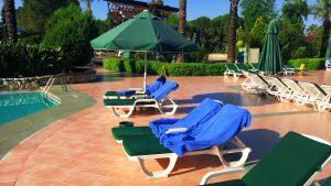 Bezette strandstoelen met handdoeken bij het zwembad
