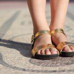 Vrouw met slippers op een mozaīek
