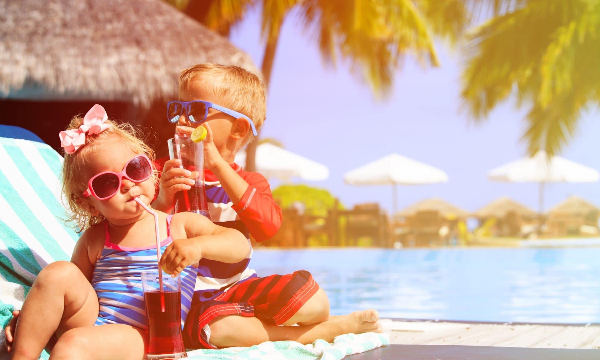 Kinderen drinken een sapje bij een zwembad