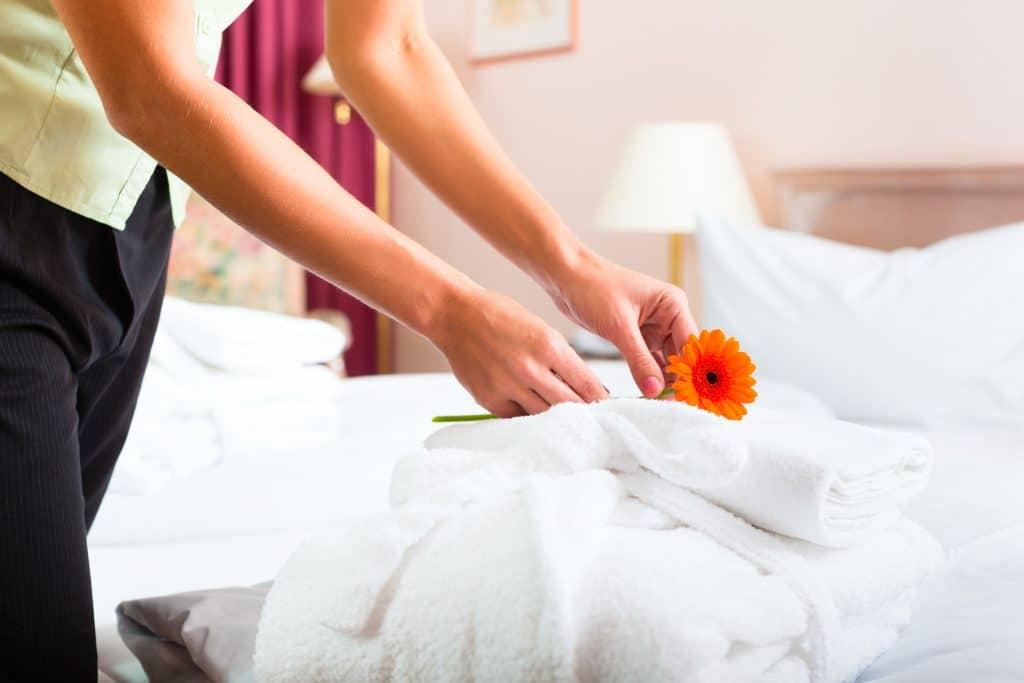 Kamermeisje legt bloem neer op handdoeken