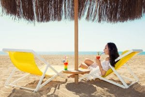 Vrouw met cocktail op het strand onder een parasol