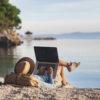 Jonge vrouw met laptop op een strand