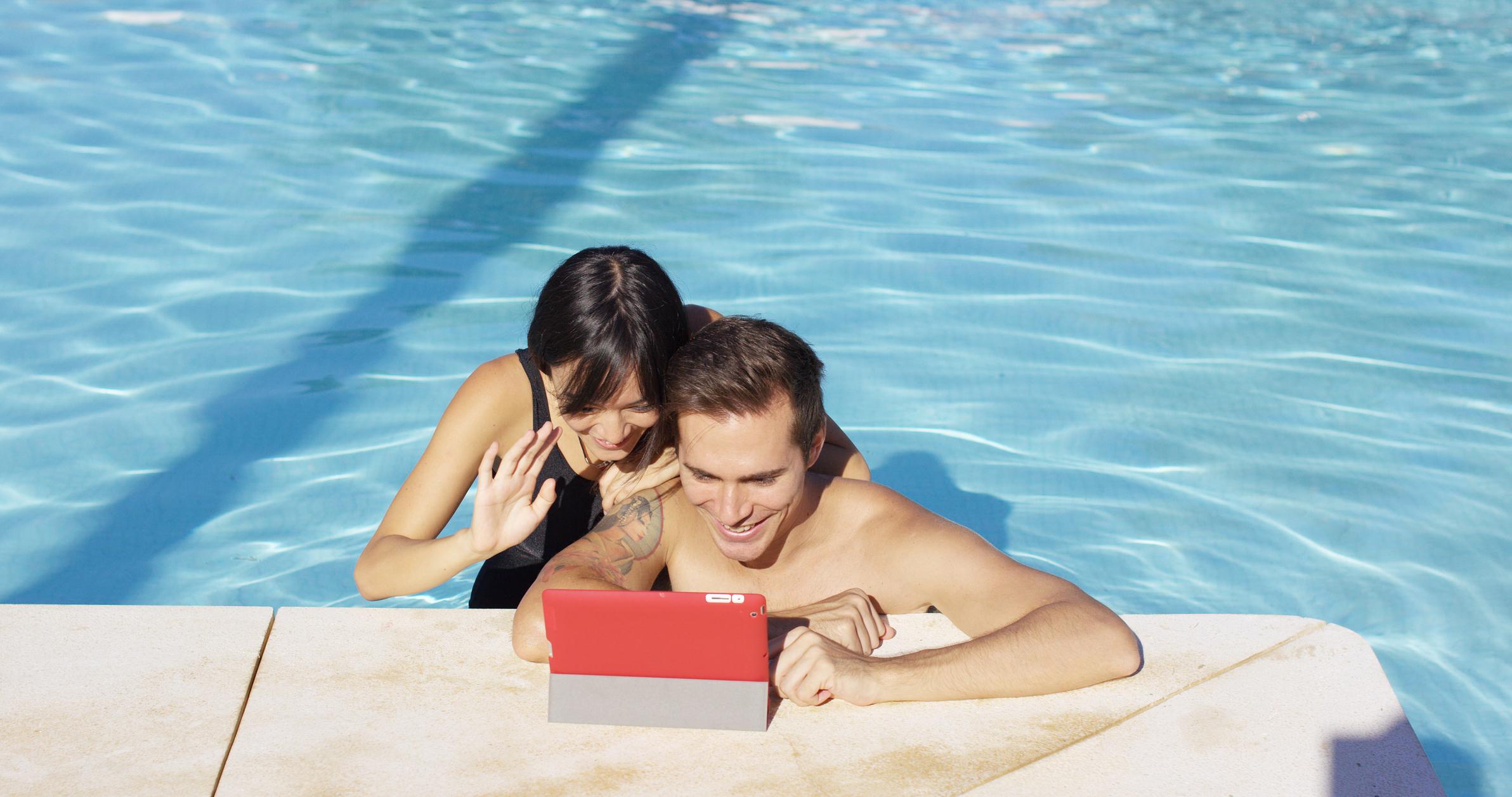 Vrouw en man in het zwembad zwaaien naar een tablet