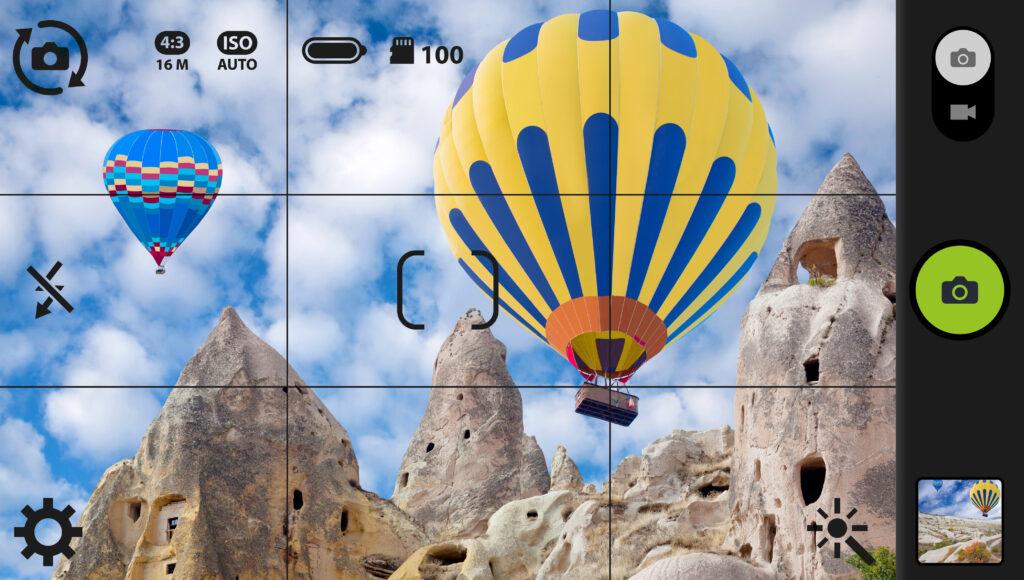 Smartphone met gridlines maakt een foto van luchtballonnen in Cappadocië, Turkije