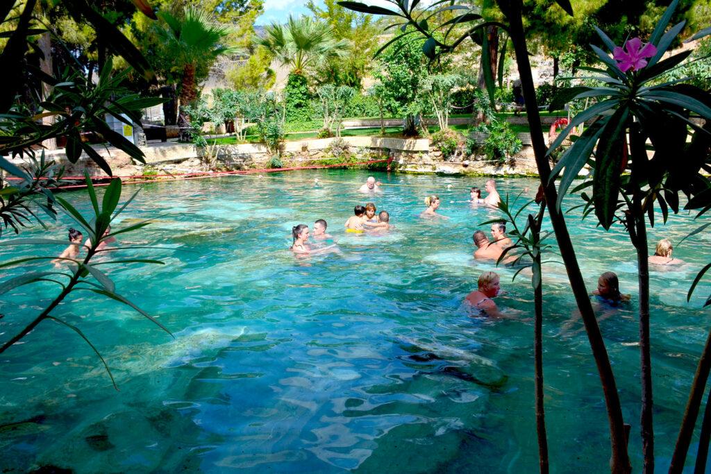 Mensen zwemmen in het antieke Cleopatra's zwembad met thermaal water in Hierapolis, Turkije