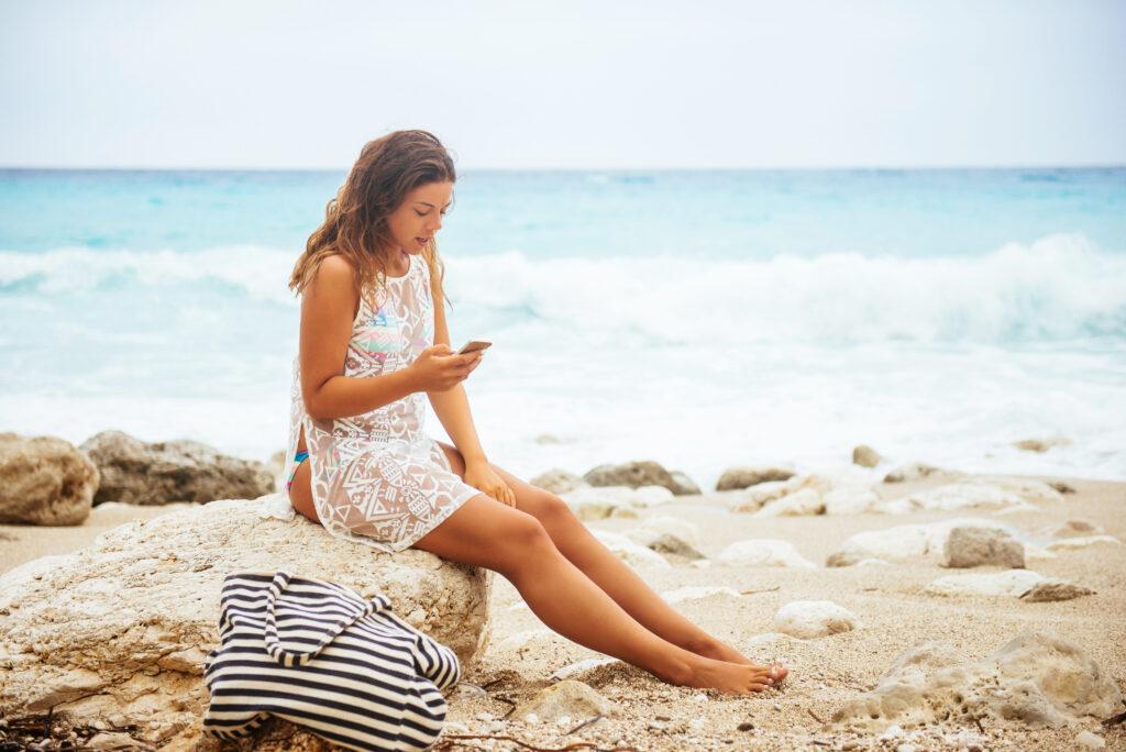 Vrouw met telefoon op het strand