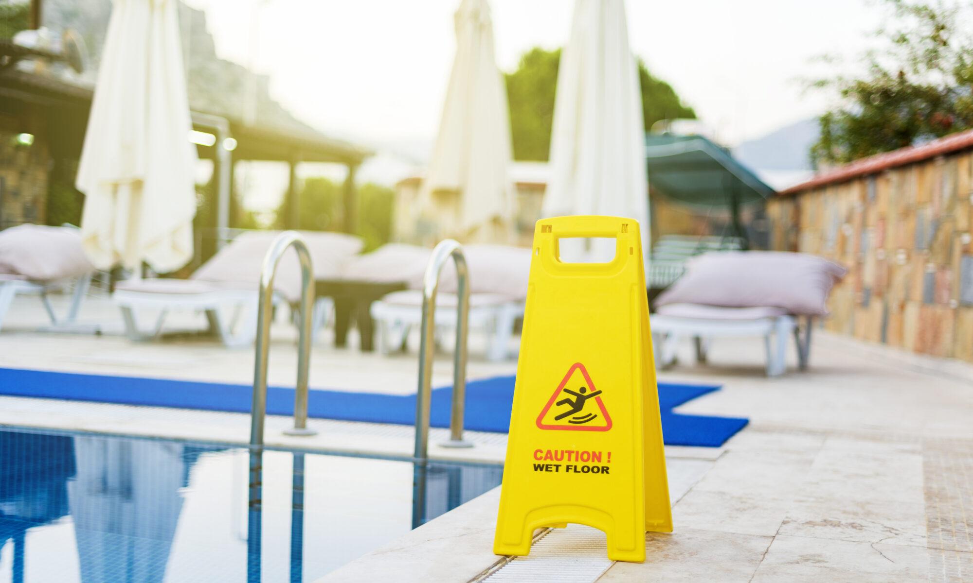 Waarschuwingsbord voor natte vloer bij een zwembad