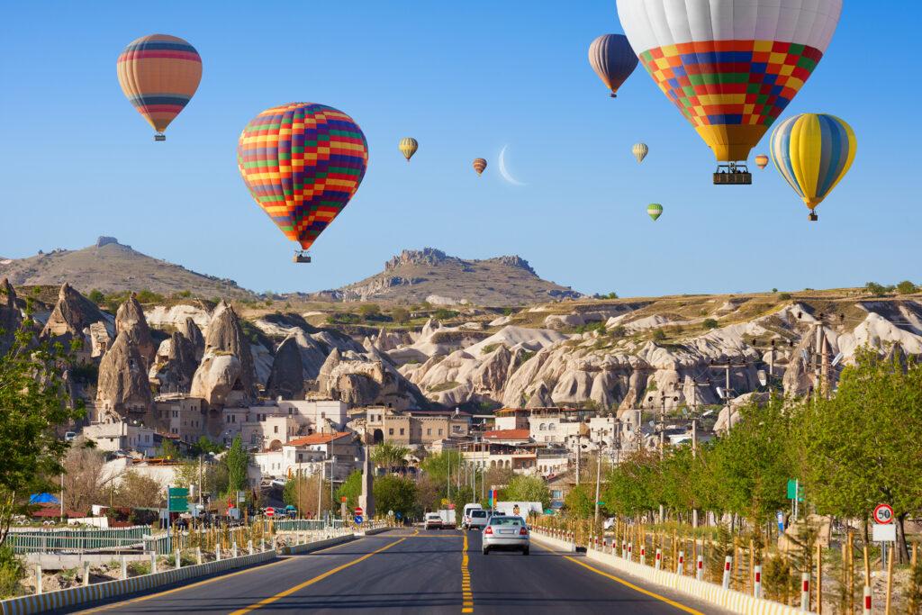 Heteluchtballonnen boven een weg in de plaats Göreme in Cappadocië, Turkije