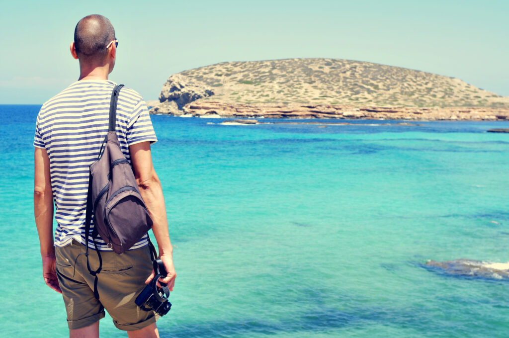 Man met rugzak kijkt naar een eiland in zee