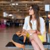 Vrouw met bril en tas wacht op een bankje op het vliegveld