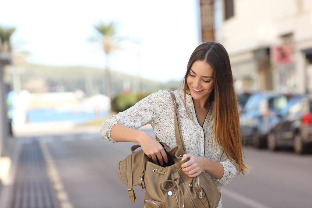 Vrouw op straat zoekt iets in haar tas
