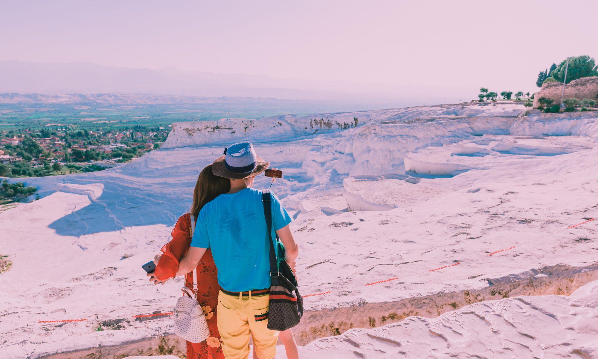 Vrouw en man kijken uit over de terrassen van Pamukkale