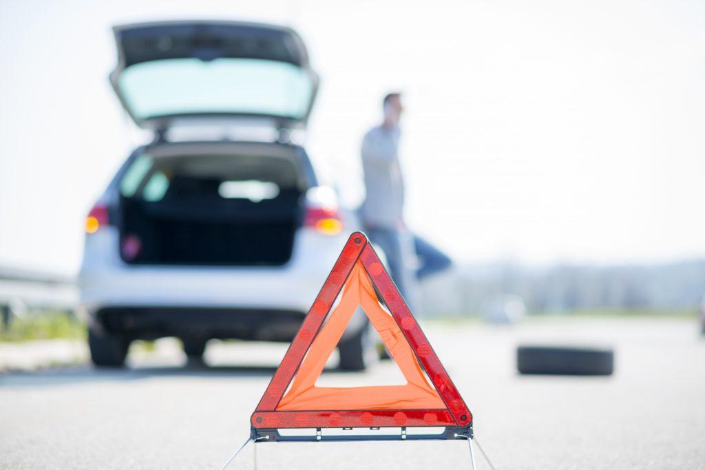 Auto met problemen en gevarendriehoek op de weg